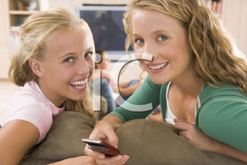 Royalty Free Photo of Teens in Front of a TV Using a Cellphone