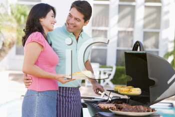 Royalty Free Photo of a Man and Woman Barbecuing
