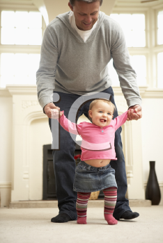 Royalty Free Photo of a Father Helping His Daughter Walk