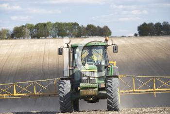 Royalty Free Photo of a Tractor Spraying a Field