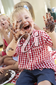Group Of Children Eating Cake At Outdoor Tea Party