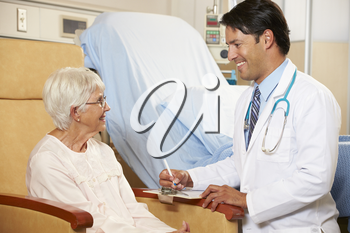 Doctor Taking Notes From Senior Female Patient Seated In Chair By Hospital Bed