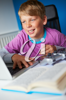 Boy Studying In Bedroom Using Laptop