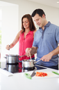 Hispanic Couple Cooking Meal At Home Together
