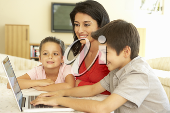 Hispanic Mother And Children Using Computer At Home