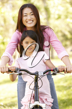 Asian mother and daughter on bicycle in park