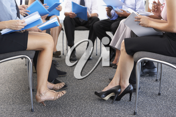 Detail Of Businesspeople Seated In Circle At Company Seminar