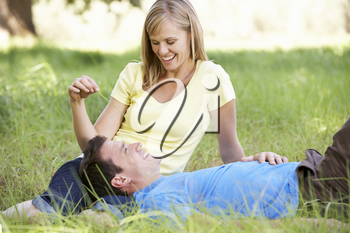 Couple Relaxing In Sunny Summer Field