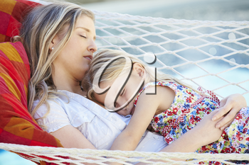 Mother And Daughter Sleeping In Garden Hammock Together