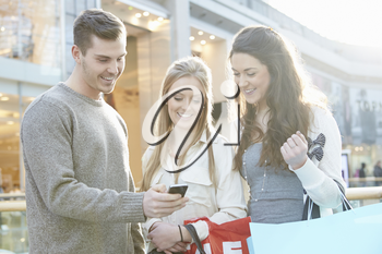 Group Of Friends Shopping In Mall Looking At Mobile Phone
