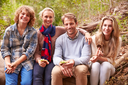 Parents and teenage kids eating outdoors in a forest, portrait