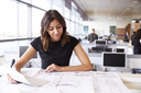 Young female architect working with blueprints in an office