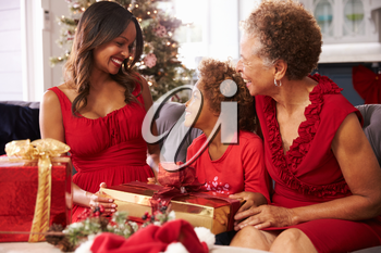 Girl With Grandmother And Mother Opening Christmas Gifts
