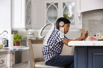 Young Asian Boy Playing Game On Mobile Device In Kitchen