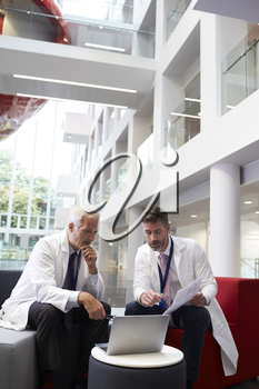 Two Doctors Having Meeting In Hospital Reception Area