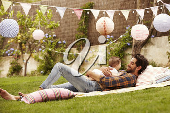 Father With Baby Relaxing On Rug In Garden Together