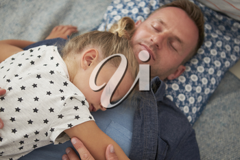 Father And Daughter Lying On Floor Asleep Together