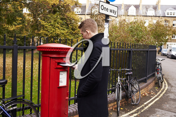 Man Posting Letter In Red British Postbox
