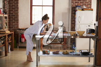 Young woman in pyjamas using laptop in kitchen, full length