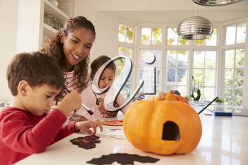 Mother And Children Making Halloween Decorations At Home