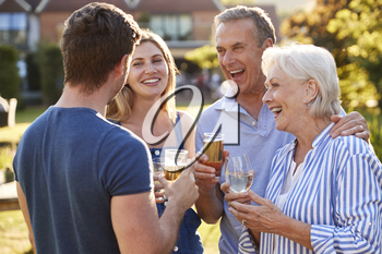 Parents With Adult Offspring Enjoying Outdoor Summer Drink At Pub