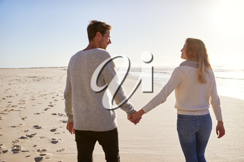 Rear View Of Loving Couple Walking Along Winter Beach Together