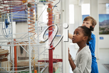 Two kids looking at a science exhibit, waist up