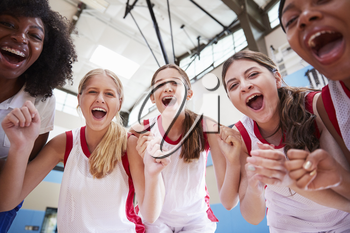 Portrait Of Female High School Basketball Team Celebrating With Coach
