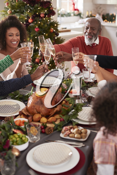 Black grandfather making a toast with his family at the Christmas dinner table, elevated view