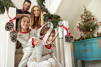 Portrait Of Excited Family Wearing Pajamas Sitting On Stairs On Christmas Morning