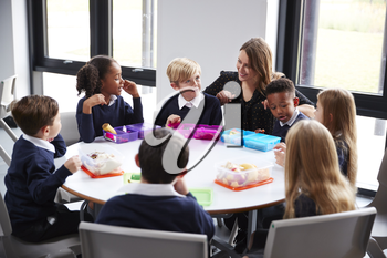 Female teacher kneeling to talk to a group of primary school kids sitting together at a round table eating their packed lunches