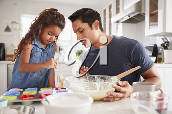 Young girl standing at the kitchen table making cakes with her father, filling cake forms, close up