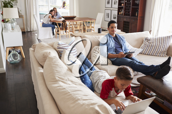 Pre-teen boy lying on sofa using laptop, dad sitting with tablet, mum and grandma in the background