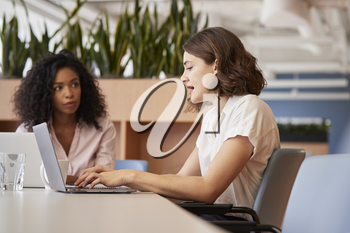 Two Businesswomen Working On Laptops Sitting At Table In Modern Open Plan Office