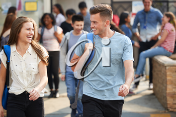 Group Of Smiling Male And Female College Students Walking And Chatting Outside School Building