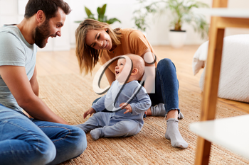 Parents Sitting On Floor At Home Playing With Baby Son