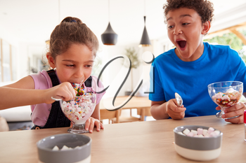 Children In Kitchen At Home Eating Ice Cream Desserts They Have Made