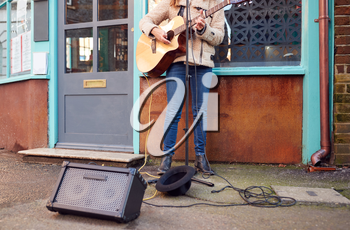 Close Up Of Female Musician Busking Playing Acoustic Guitar Outdoors In Street