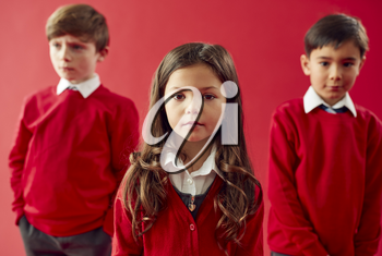 Group Of Elementary School Pupils Wearing Uniform Against Red Studio Background