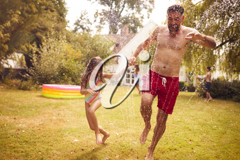 Father And Daughter Run Through Water From Garden Sprinkler Having Fun Wearing Swimming Costumes