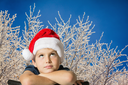 The charming seven-year-old boy in red Santa Claus cap thoughtfully looks up. The picture is made against the snow-covered New Year's wood