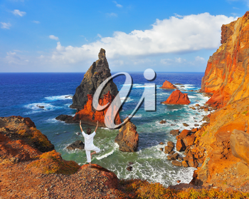 The woman ashore in a white suit for yoga carries out a pose Tree. Atlantic storms. Colorful pinnacles lit sunset. Arid eastern tip of the island of Madeira