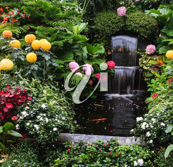 Gorgeous three-stage fountain surrounded by flowers. Butchart Garden Park on Vancouver Island, Canada