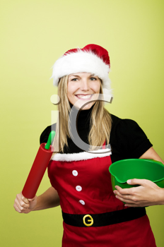 Woman in Christmas apron holding baking utensils
