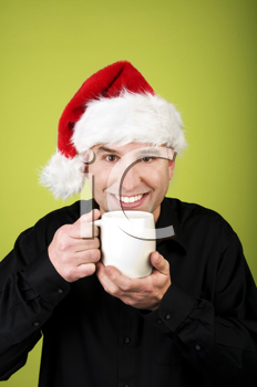 Royalty Free Clipart Image of a Smiling Man in a Santa Hat Holding a Mug
