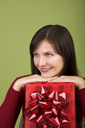Royalty Free Photo of a Woman Leaning on a Christmas Gift