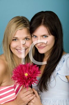 Royalty Free Photo of Two Women Holding a Pink Flower