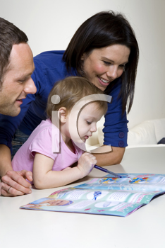 Royalty Free Photo Image of a Couple Helping Their Child With an Activity Book