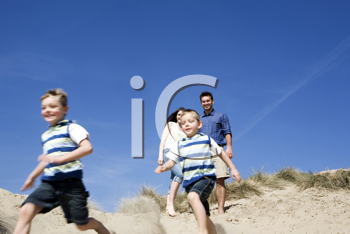 Royalty Free Photo of a Couple on the Beach With Their Children