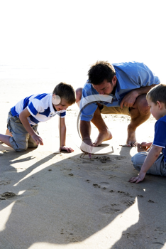 Royalty Free Photo of a Man and His Sons Drawing in the Sand